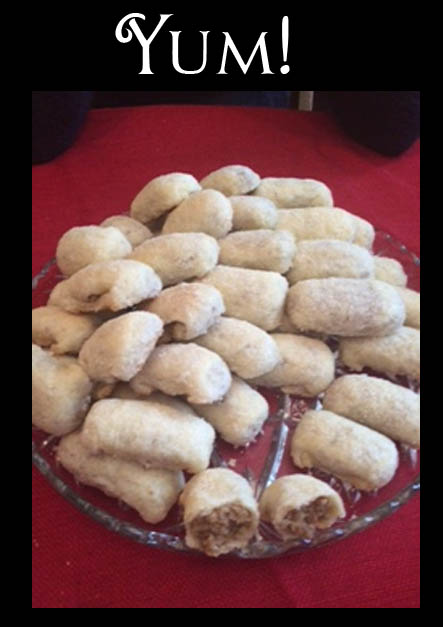 """Picture of nut roll cookies piled on a plate with the word """"Yum!"""" over top of it"""